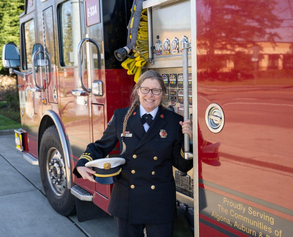 Fire Marshal Karen Stewart stands next to a fire truck in her dress uniform.