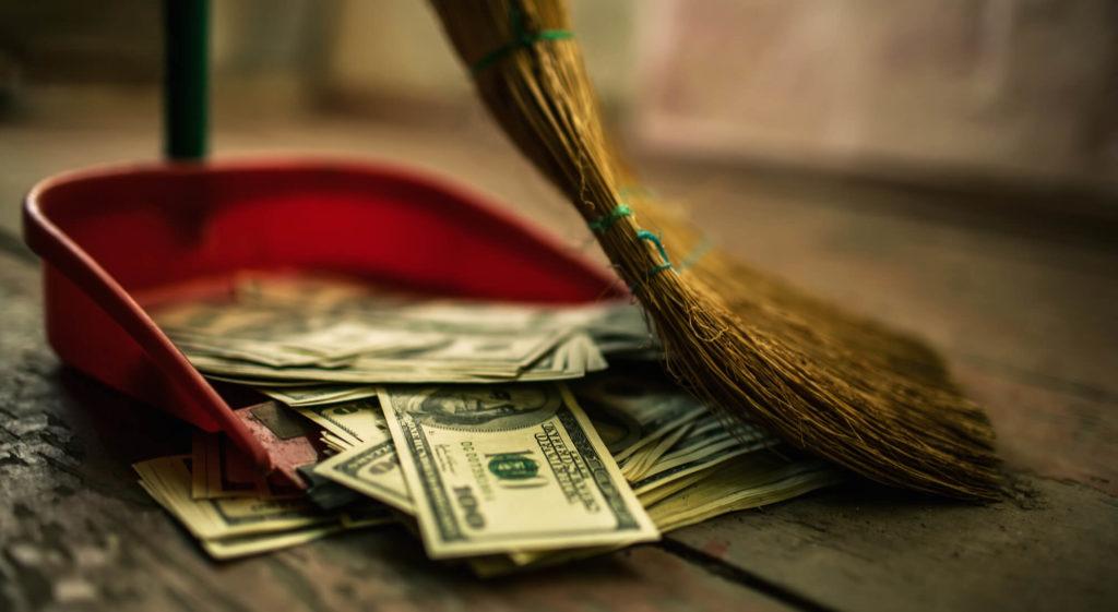 a broom sweeps 100 dollar bills into a red dustpan