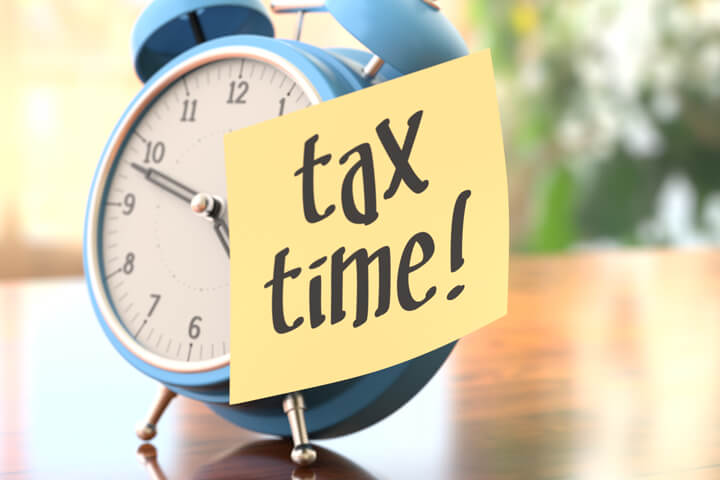 """A blue old-fashioned alarm clock with a yellow post-it note on it that says """"Tax Time!"""""""