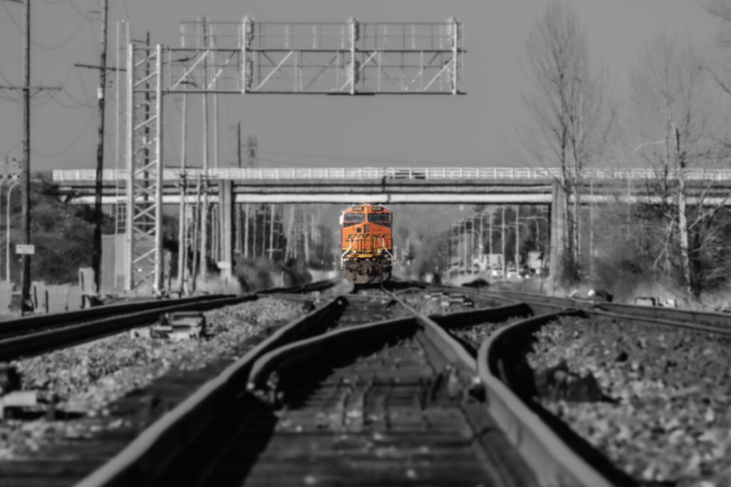 A black and white photo of a train on tracks, the train stands out as the sole thing of color a bright pop of orange in the photo