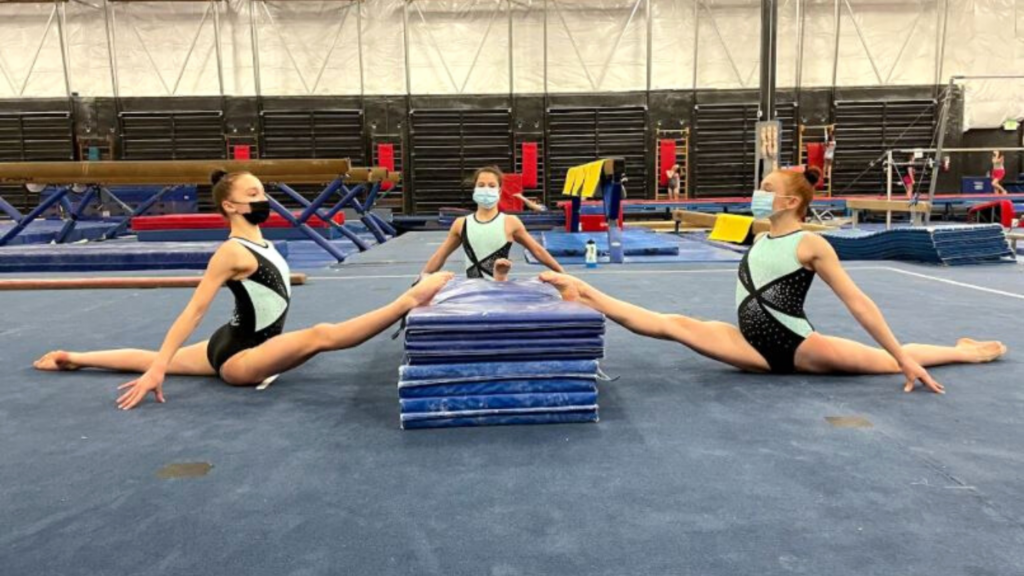 three Ascend gymnastics gymnasts do splits with their front lets lifted onto a stack of mats