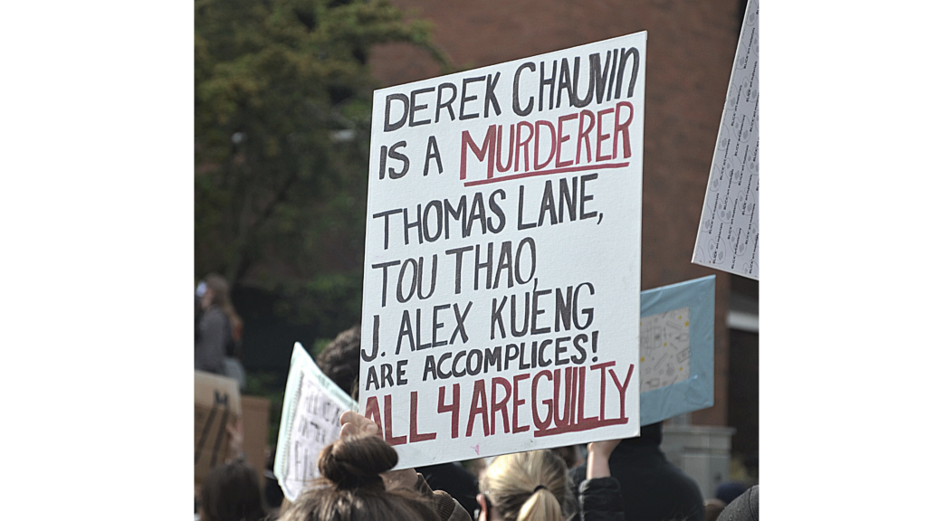 """A protester holds a sign up at the June 3 Auburn BLM rally. the sign reads """"Derek Chaubin is a Murderer. Thomas Lane, Tou Thoa, J. Alex Kueing are accomplices. All 4 are guilty"""""""