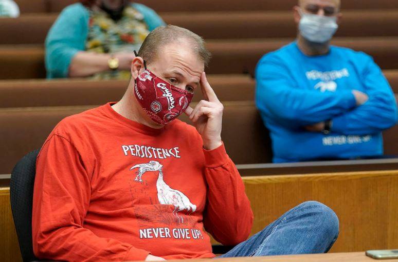 """Tim Eyman sits at in court with his hand to his forehead, looking downward. He wears a red and gray WSU mask and a 'Persistence Never Give Up"""" shirt."""