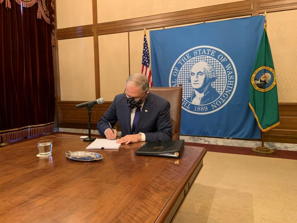 WA Governor Jay Inslee, wearing a mask and sitting alone at the end of a long table, signs a bill into law