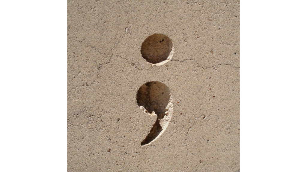 a semicolon etched in tan stone