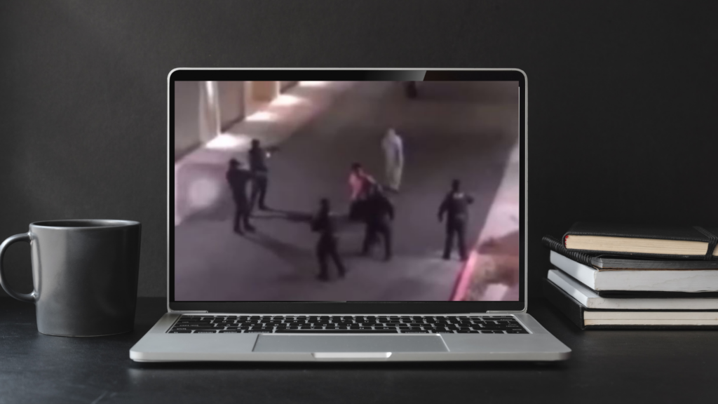 A screengrab of the video is on a laptop on a desk