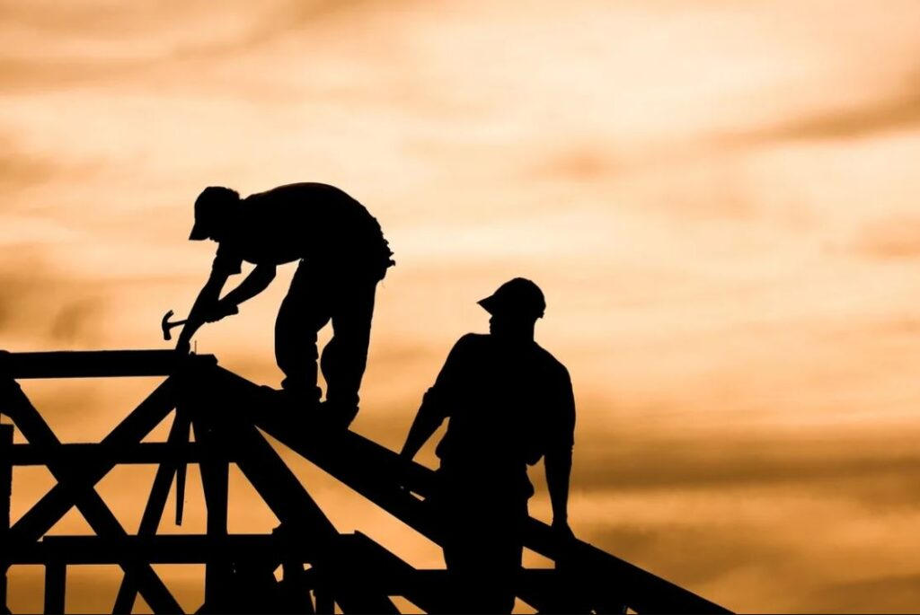 twoconstruction workers work on top of the frame of a home. The workers are silhouettes to a vibrant orange sky.