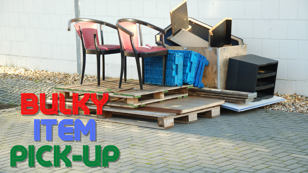 """items stacked against a wall and on pallets, waiting to be picked up. the words """"Bulky Item Pick-up"""" are in the lower left corner"""