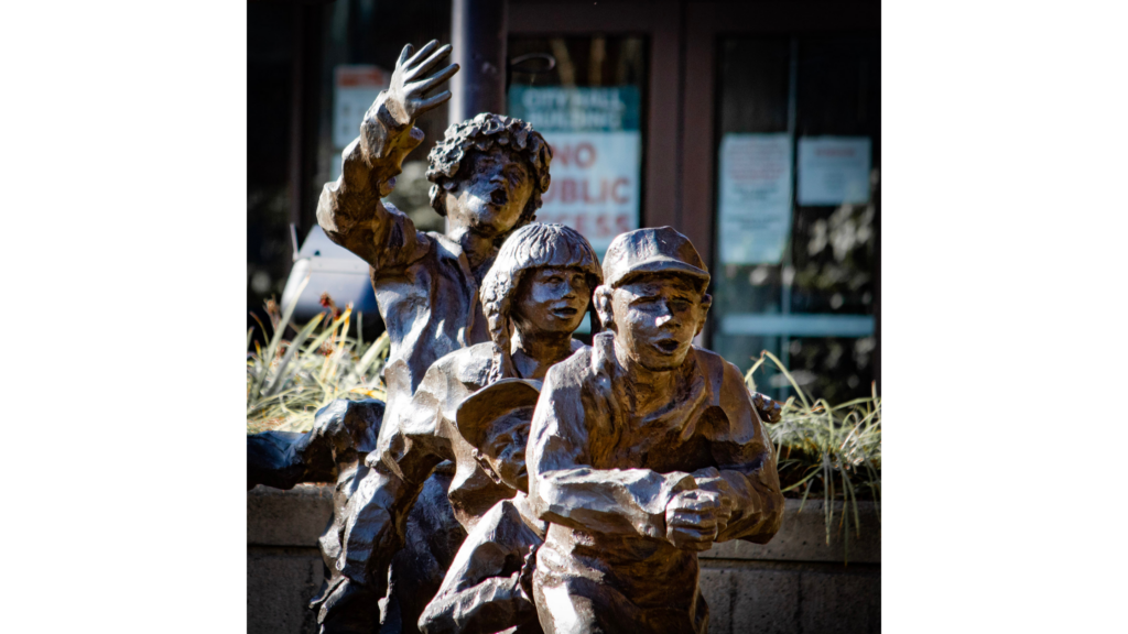 A metal statue of 4 children in a line playing. The statue is in front of Auburn City Hall, which can be seen out of focus in the background.