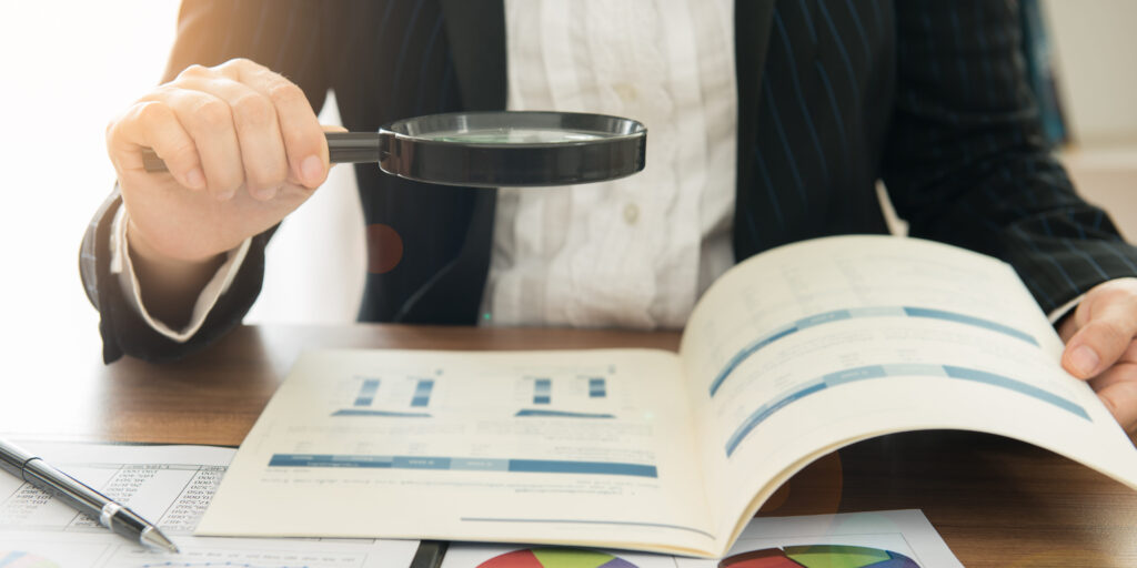 an individual holds a magnifying glass over a financial report booklet, additional pages of reports on the desk below the booklet