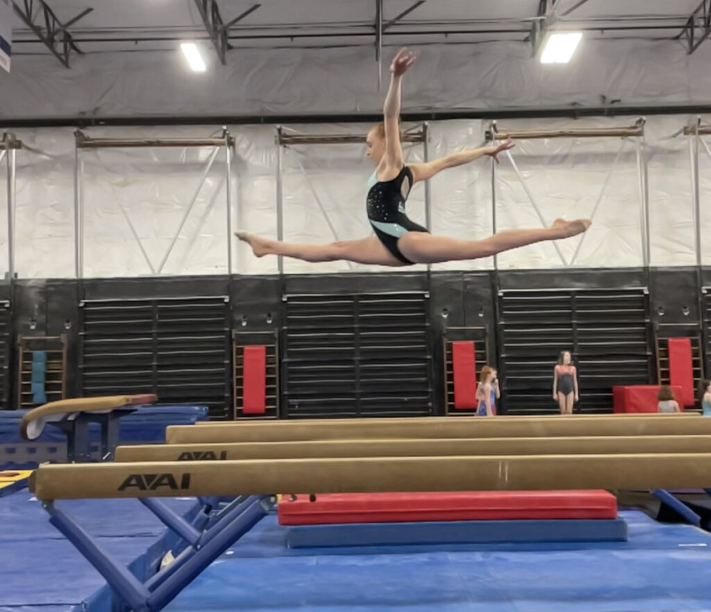 Isabelle Futch is captured mid-air doing the splits on the balance beam at Ascend Gymnastics