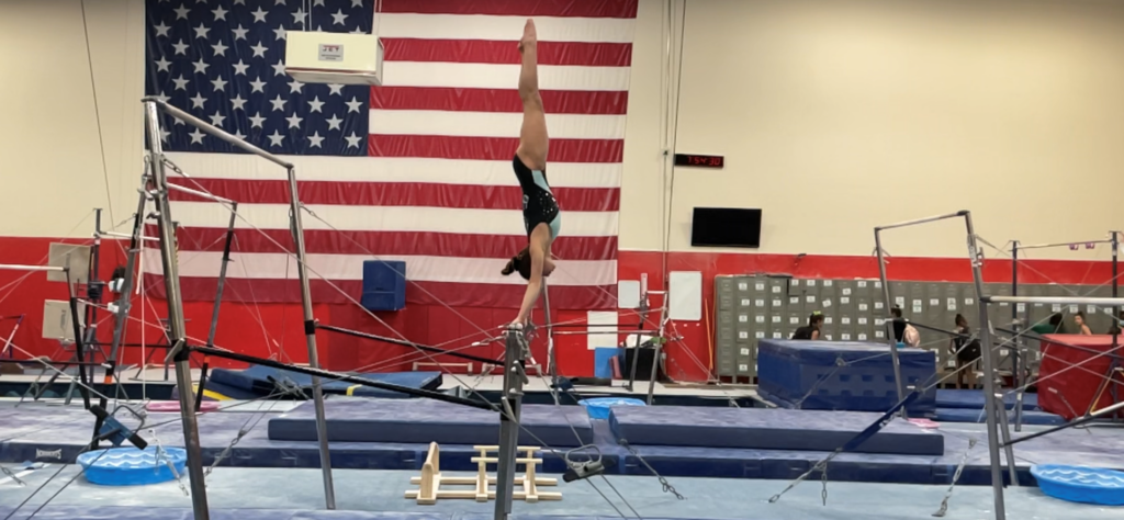 Jocelyn Sasson practices on the uneven bars at Ascend Gymnastics in Auburn, the photo captures here vertical on the high bar.