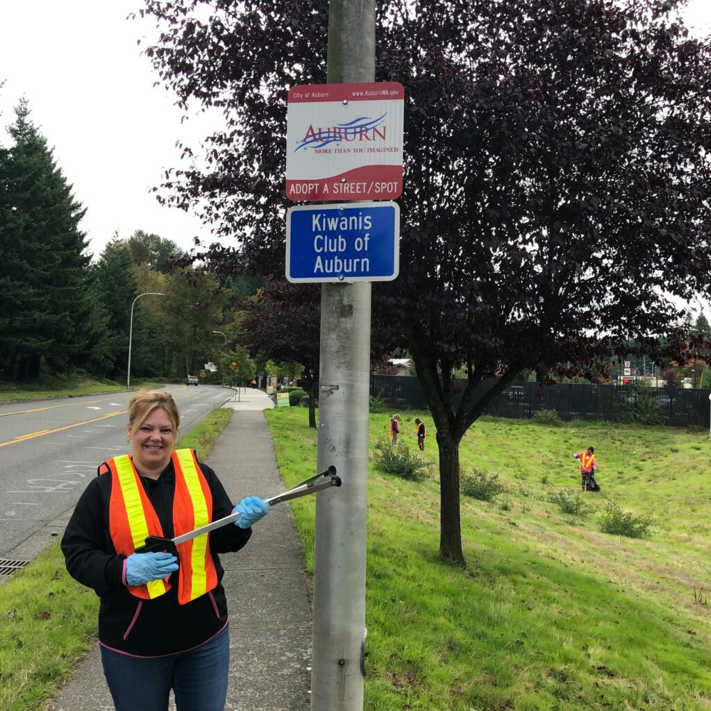 A Kiwanis member stands under the service group's Adopt-a-Street sign while holding a garbage grabber.