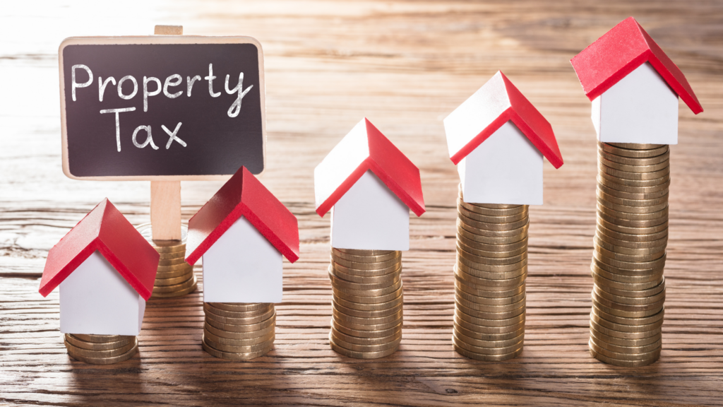 """small houses sit on stacks of coins that increase in size. A """"property tax"""" sign sits near the lowest stacks."""