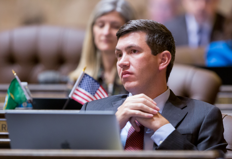 Rep. Drew Stokesbary of Auburn leans back in his chair at his desk in the State House chamber. his hands folded at his chest in front of him. Stokesbary looks off to the side with a concerned expression