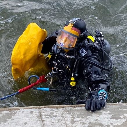 A diver comes out of the water at the dock