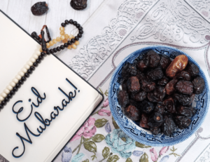 An open prayer book sits on a prayer rug with prayer beads and a bowl of dates next to it. Eid Mukarak! is written on the page of the book.
