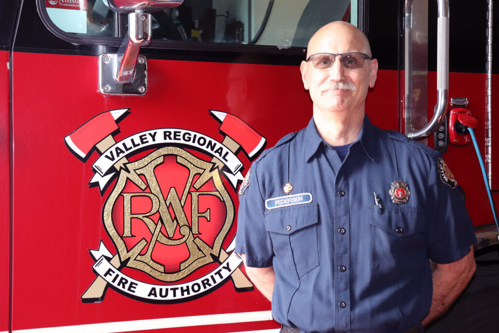 VRFA Firefighter Neil Pedersen stands with his hands behind his back in front of a VRFA fire engine.