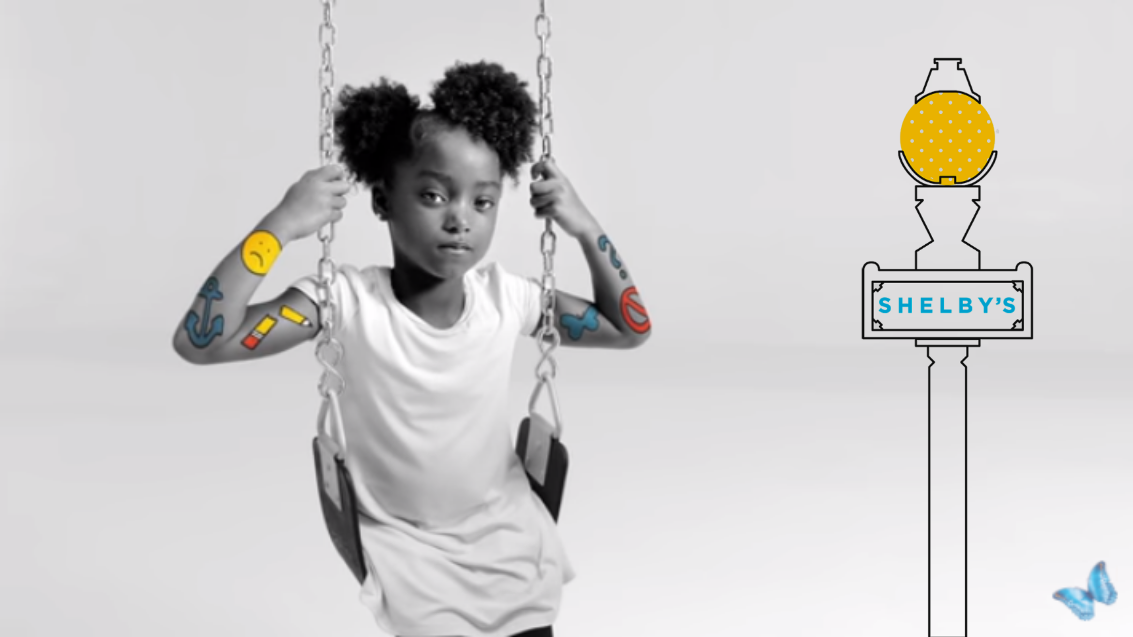 """A little girl sits on a swing, holding its chains. Her arms have colorful icons symbolizing her emotions. A light pole with """"Shelby's"""" is to her right."""