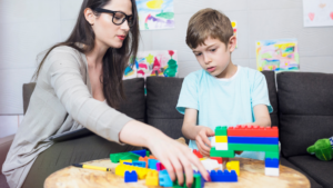 an adult female sits at a table with a young boy, playing with lego blocks in a professional or educational setting. A clip board sits in the woman's lap implying this is an evaluation or therapy session.