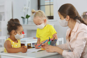 Teacher and children with face mask at school covid19 lesson after quarantine and lockdown