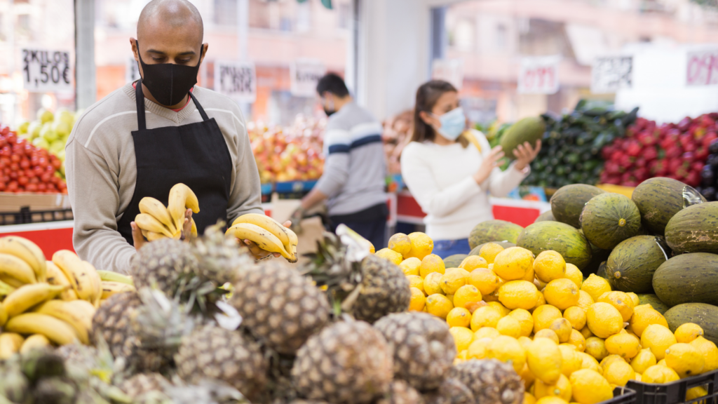 a male grocery store worker wears a cloth mask as he restocks produce