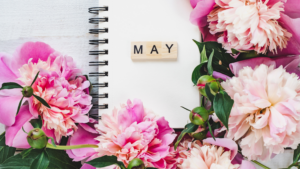 Large fluffy pink flowers surround a sspiral notepad with three scrabble letters spelling out MAY laying on top of it.