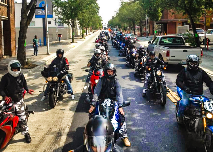 two long rows of motorcycles line a city street, ready to ride. Two motorcycle guides are to the left of the group.