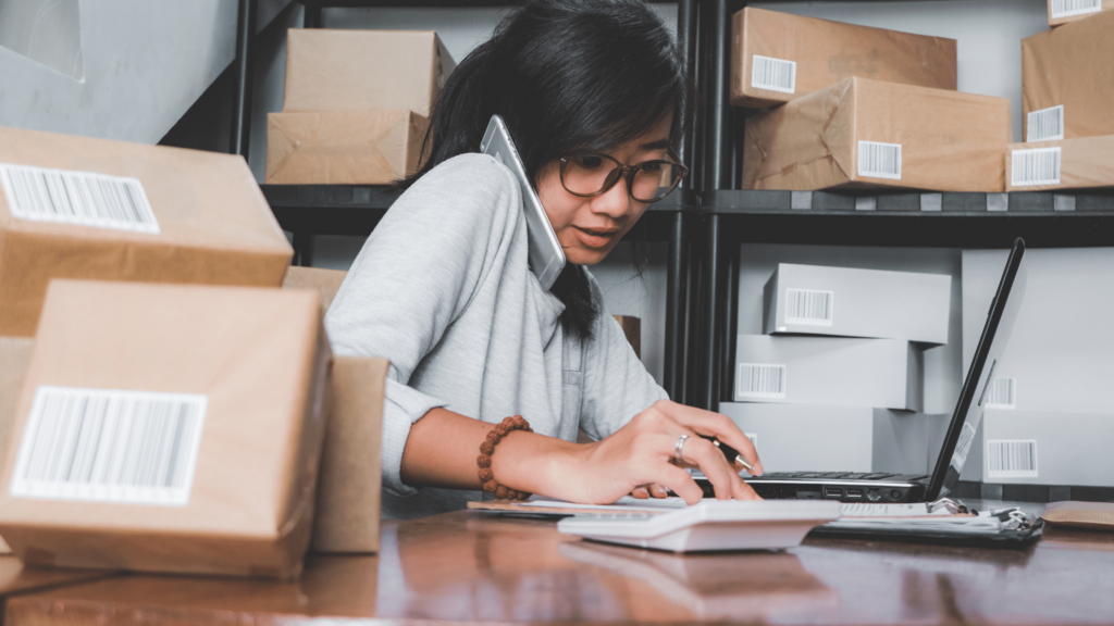 a woman sits at a desk on the phone, a laptop in front of her packages on the desk and on a shelf behind her.