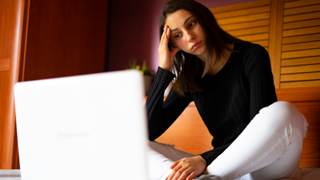 A young woman sits cross legged in front of a laptop looking dejected, her hand on her forhead