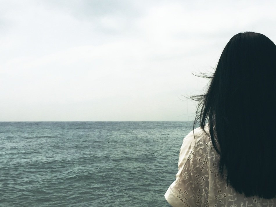 a woman with long dark hair stands with her back to the camera, looking outward toward a calm ocean