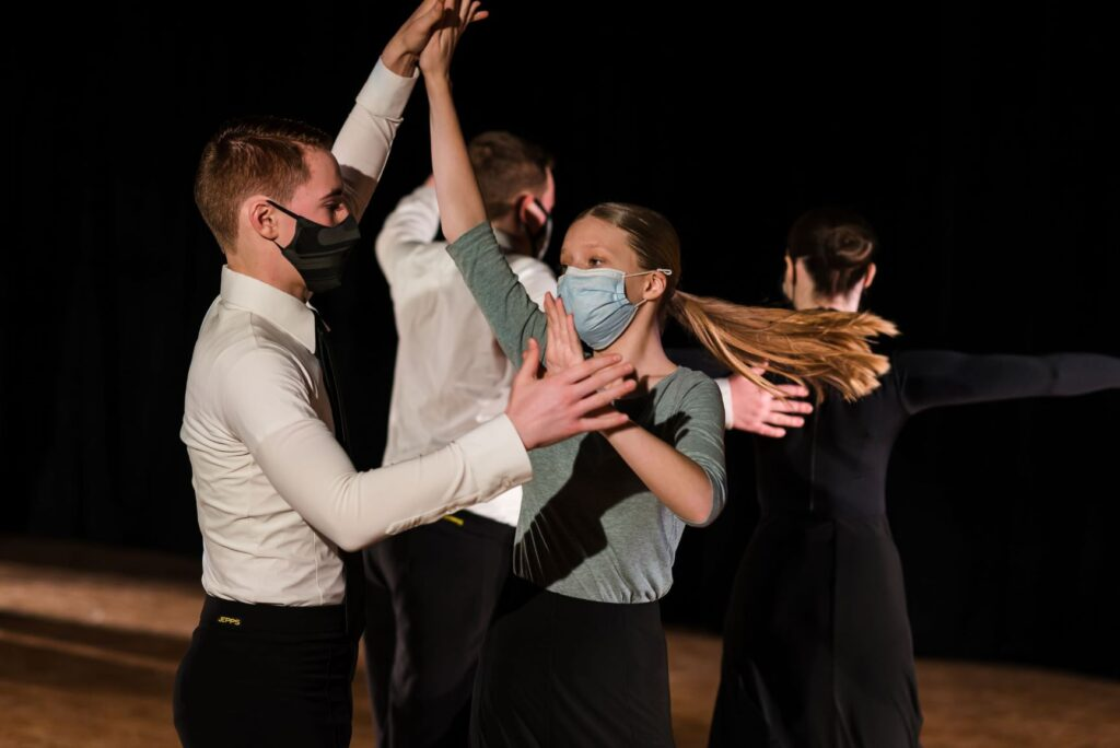 Two couples dance on the floor of a ballroom, the front couple is captured in mid-turn.  The female's long ponytail stretches out as she turns around.