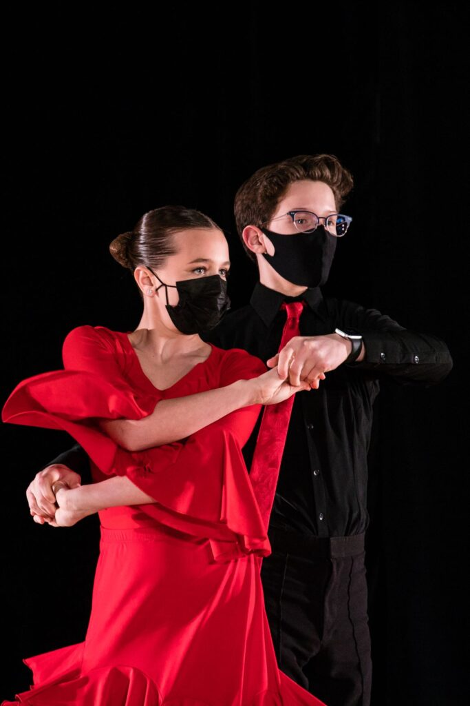 A couple are captured mid-dance. The female wears a red dress, the male a black shirt and pants and red tie.