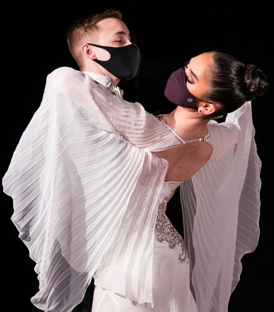 Two ballroom dancers kiss each other in a box pose.  The female of the pair wears a white dress with oversized bell sleeves that drape the pair.
