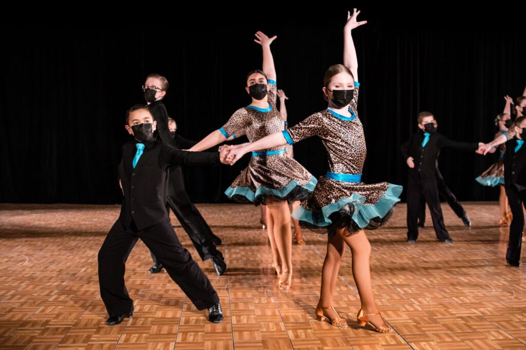 Two couples wearing vibrant costumes dance together in two rows