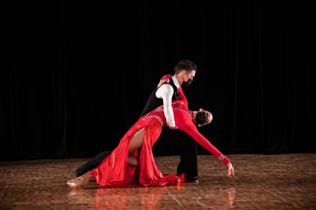 A male dancer holds a female dancer as he dips her back, her arm extending out toward the ground