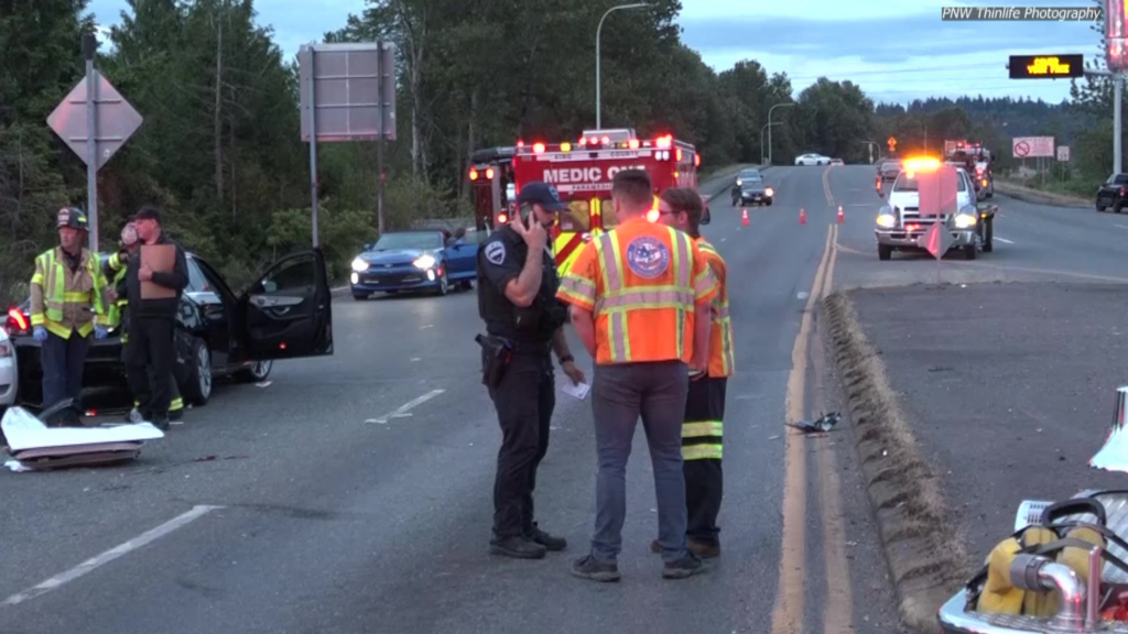 Police and medics talk in a huddle on scene of a motorvehicle accident