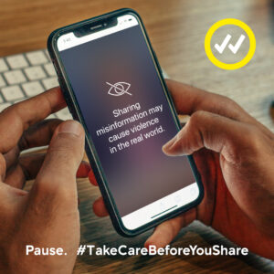 A person holds a phone with a warning that sharing false information can caue violence in the real world