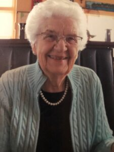A photograph of an elderly White female sitting in a chair, smiling.