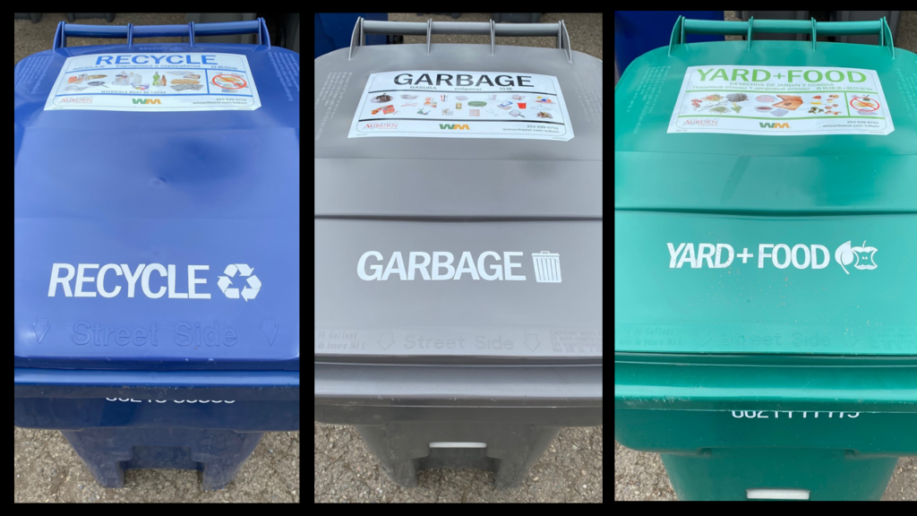 The tops of three Waste Management containers in a row. A blue container labeled Recycling, a Gray container labeled Garbage, and a green container labeled Waste.