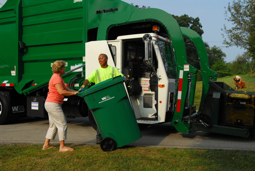 A Waste Management truck is parked next to the curb, the Waste Management driver speaking to a female customer who is posed to bring in her container.