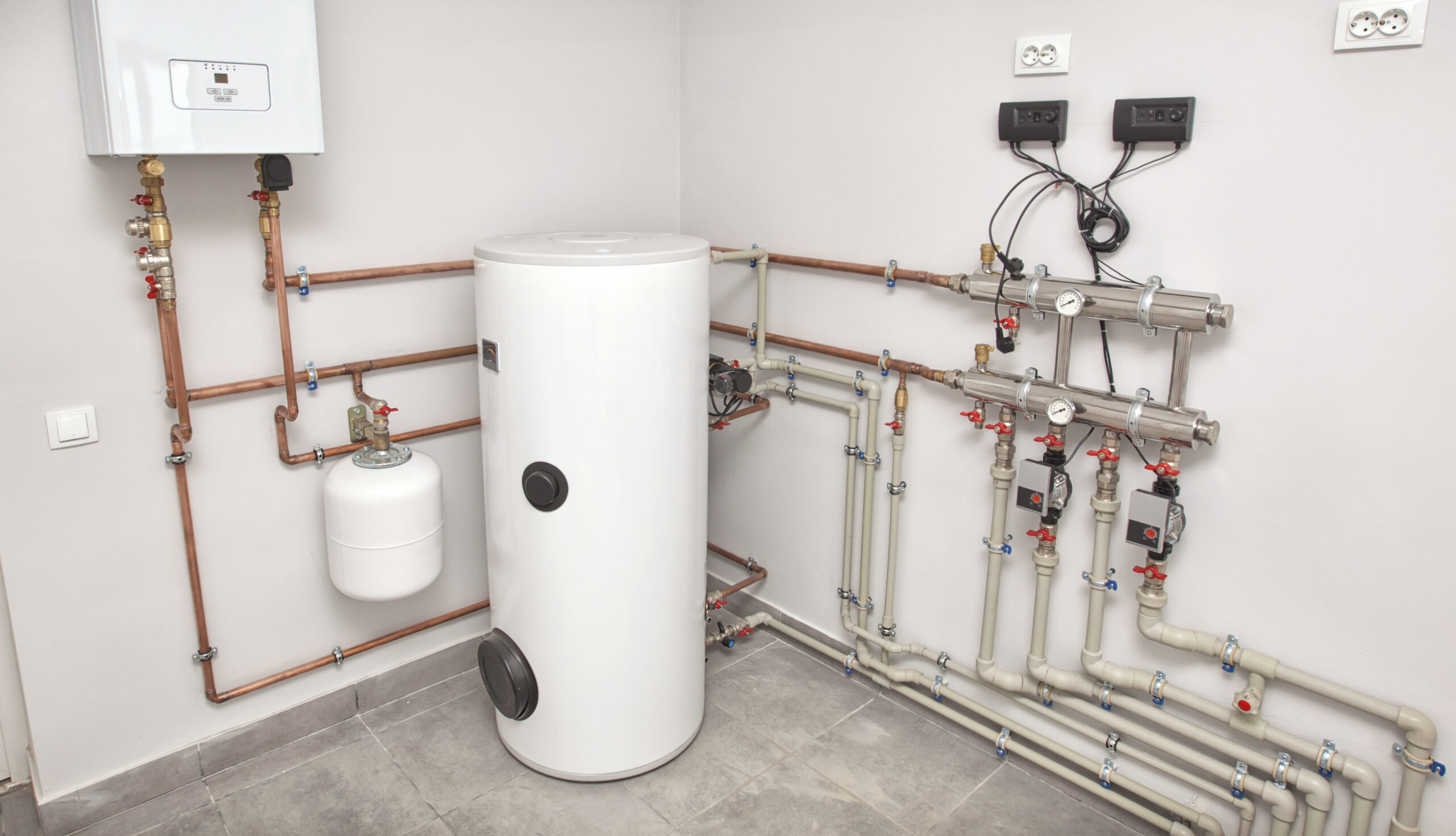 The boiler room with a lot of different equipment as a boiler, heater,pipes, expansion tank and other