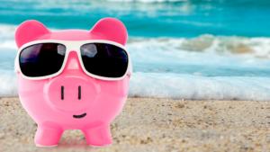 a piggy bank wear sunglasses while on a beach