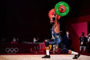 Weightlifter Harrison Maurus hoists a heavy barbell over his head, one leg bent slightly at the knee and the other behind him in a brace position.