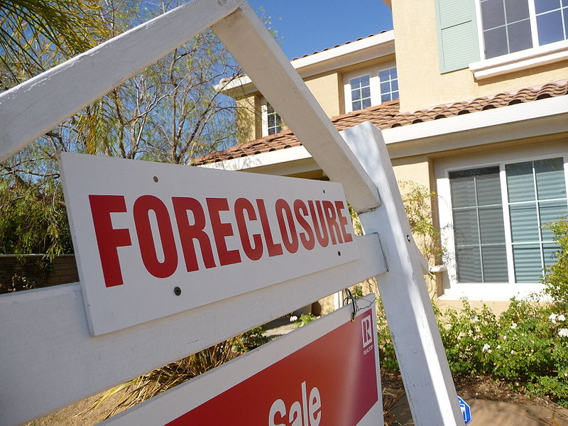 An up close photo of a real estate foreclosure sign in front of a single family home