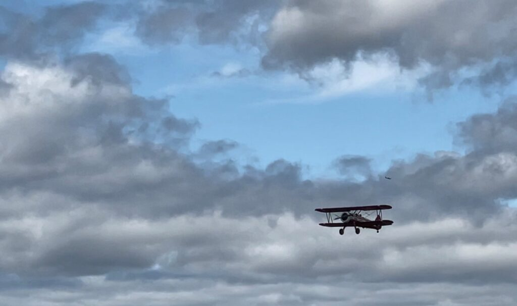 A restored Boeing Stearman biplane flies through ablue sky with gray clouds.