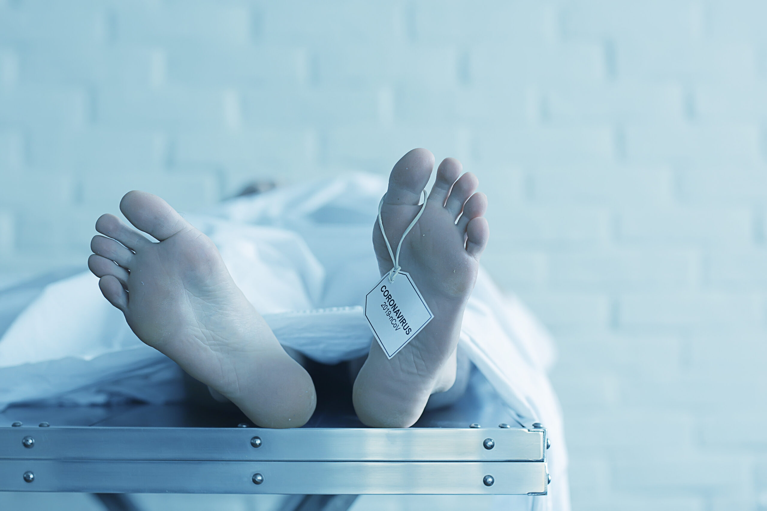 """male covered on table in morgue, his feet sticking out with toe tag that reads """"coronavirus 2019"""""""