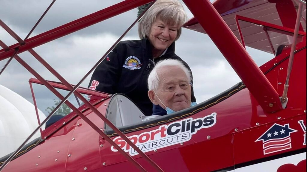 Darrell Campbell sits in a restored biplane with a female smiling behind him
