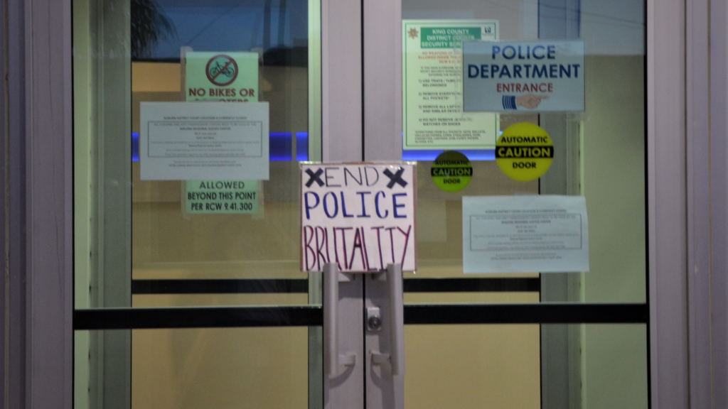 """A sign reading """"End Police Brutality"""" sits on the doors to the Auburn Justice Center"""