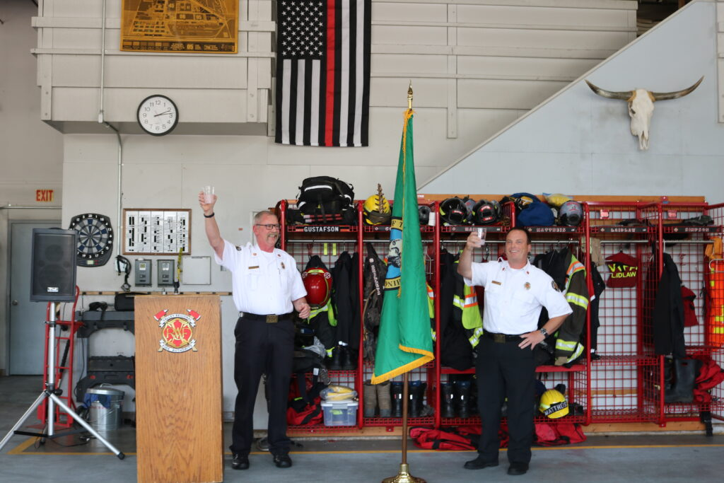 Retired VRFA Chief Brent Swearingen and new VRFA Chief Brad Thompson both raise a glass in a toast during the changing of the command ceremony